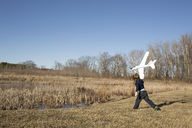 Playful boy flying model airplane while standing on field against clear sky - CAVF43110