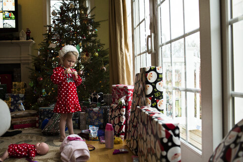 Girl standing by Christmas tree at home - CAVF43140