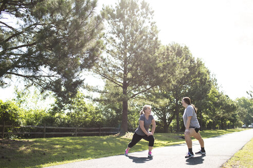 Full length of mother and daughter stretching legs while exercising on footpath at park - CAVF43143