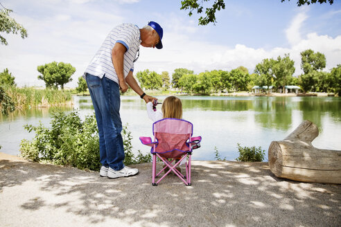 Grandfather and granddaughter fishing at lakeshore - CAVF43215