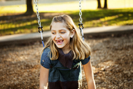 Cheerful girl playing on swing at park during autumn - CAVF43416