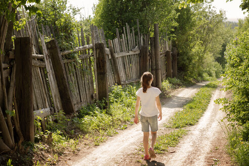 Rear view of girl walking on dirt road by wooden fence during sunny day - CAVF43455
