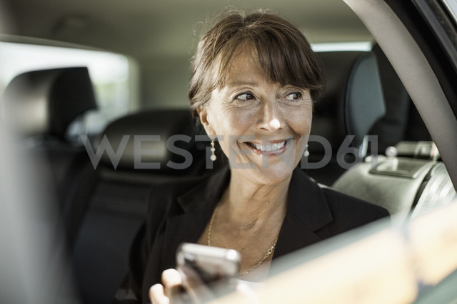 Happy businesswoman holding mobile phone looking out through taxi window - MASF05607