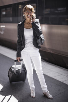 Happy businesswoman with suitcase using mobile phone on railroad station platform - MASF05610