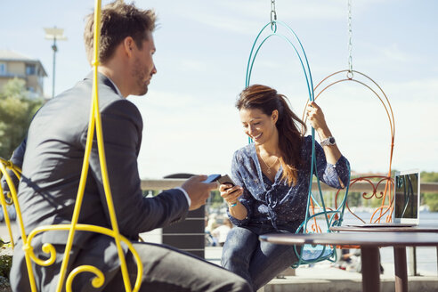 Happy businesswoman using mobile phone on swing while sitting with colleague at sidewalk cafe - MASF05619