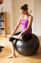 Full length of pregnant woman exercising on fitness ball at home - MASF05634