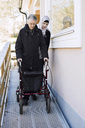 Female home caregiver helping senior woman with walking frame through passage - MASF05664