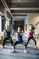 Full length of friends lifting kettlebells at health club - MASF05682