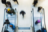 Blurred motion of people using escalator in mall - MASF05694