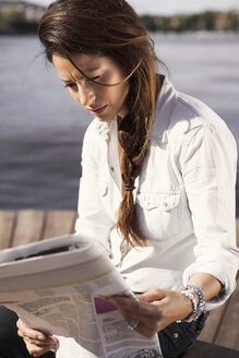 Businesswoman reading newspaper while sitting on boardwalk - MASF05718