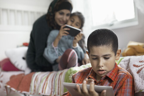Boy using digital tablet in bedroom with family in background - MASF05748