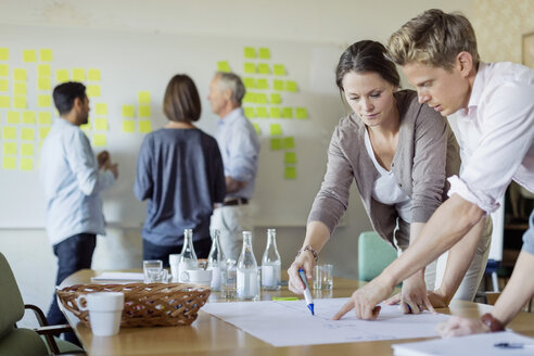 Business people discussing over blueprint at conference table - MASF05751