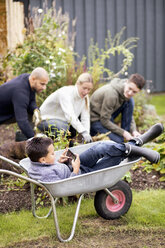 Boy using digital tablet while sitting in wheel barrow with family gardening in background - MASF05763