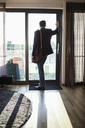 Businessman looking through window in hotel room - MASF05805