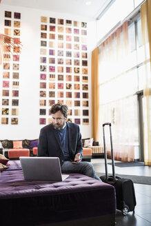Businessman using laptop in hotel lobby - MASF05817
