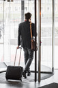 Businessman with luggage leaving hotel - MASF05820