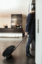 Businessman with luggage entering elevator in hotel - MASF05823