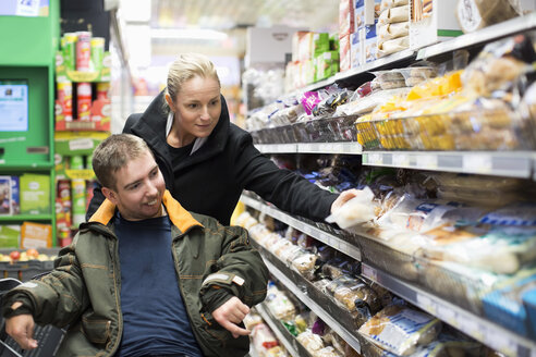 Caretaker shopping with disabled man on wheelchair in supermarket - MASF05865