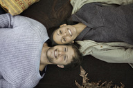 Directly above shot of couple in winter clothing lying on blanket while camping - MASF05868