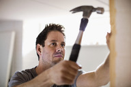 Carpenter hammering nail into wooden plank - MASF05889
