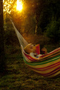 Young woman reading book while lying on hammock at park - MASF05895