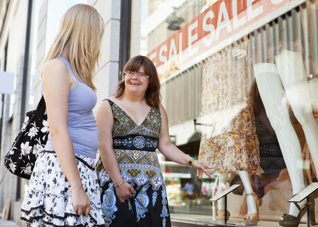 Woman with down syndrome and her personal assistant window shopping together - MASF05904