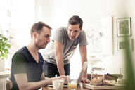 Young homosexual couple using laptop together at breakfast table in home - MASF05934