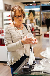 Senior woman buying cookware in shopping mall - MASF05970
