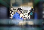 Side view of male technician wearing protective eyewear working in industry - MASF05994