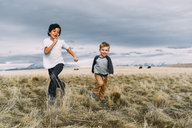 Brothers running while playing on grassy field against cloudy sky - CAVF43464