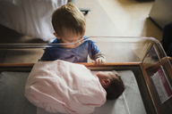 High angle view of brother looking at sister sleeping in crib - CAVF43467