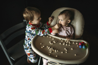 Brother feeding baby food to sister sitting on high chair in darkroom at home - CAVF43479