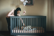 Mother looking at daughter sleeping in crib at home - CAVF43500