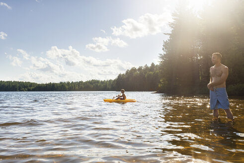 Man standing while son kayaking on lake during sunny day - CAVF43626