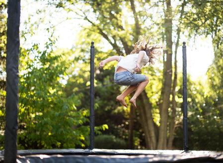 Full length of girl jumping on trampoline at park - CAVF43647