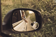 Boy looking away while sitting in car seen through side view mirror - CAVF43656