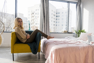 Portrait of woman relaxing on armchair in bedroom at home - CAVF43872