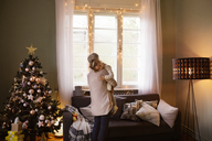 Rear view of grandmother carrying granddaughter at home during Christmas - CAVF43980