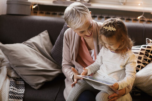 Grandmother and granddaughter using tablet computer while sitting on sofa - CAVF43983