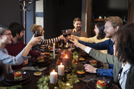 Friends toasting wine while enjoying meal at Christmas party - CAVF44025