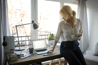 Woman using smart phone while holding salad bowl at home office - CAVF44052