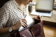 Midsection of woman putting tablet computer in purse at home office - CAVF44055