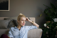 Thoughtful woman leaning on sofa at home - CAVF44061
