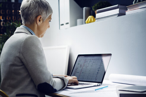 Serious architect using laptop at table in office - CAVF44076