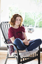 Portrait of young girl with mobile phone relaxing on armchair at home - MASF06023