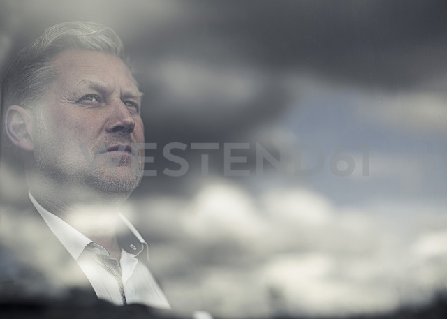 Reflection of clouds on glass window while businessman looking away - MASF06050
