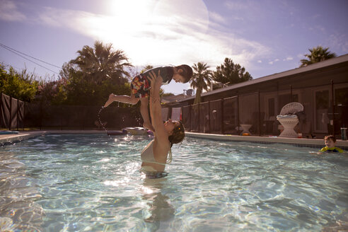 Happy mother lifting boy in swimming pool at tourist resort - CAVF44097