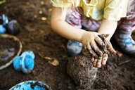 High angle view of girl playing with mud - CAVF44118