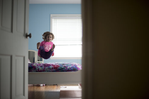 Girl jumping on bed seen through doorway at home - CAVF44145