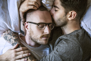 High angle close-up of loving homosexual couple lying on bed at home - CAVF44274